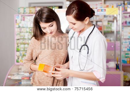 Pharmacist Woman Showing Product To Custumer