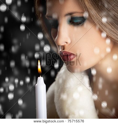 Sensual Woman Blowing Candle In Snow