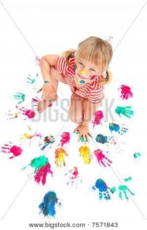Cute little girl making colorful hand prints