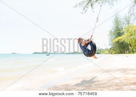 Happy woman on tire swing
