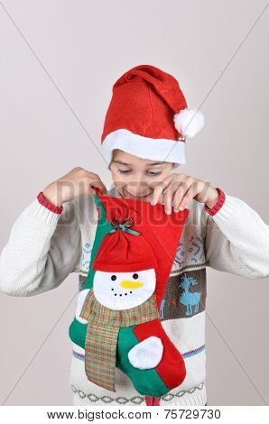 Young boy looking inside Christmas stocking