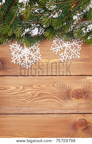 Christmas fir tree with snow and snowflake decor on rustic wooden board with paper for copy space