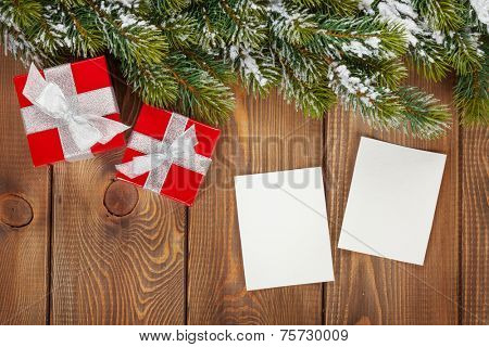 Christmas gift box and blank photo frames over wooden background with snow fir tree