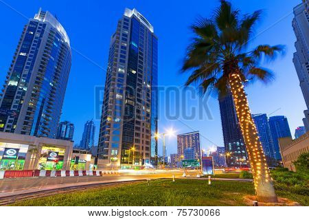 DUBAI, UAE - MARCH 30, 2014: Illuminated skyscrapers of Dubai Marina at night, United Arab Emirates. Dubai Marina is a district with artificial canal city who accommodates more than 120,000 people.