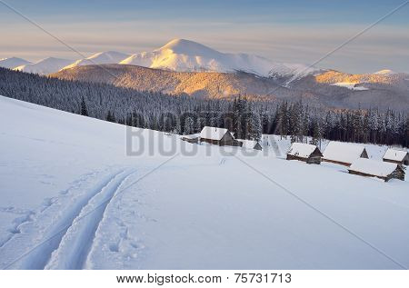 Morning landscape in the mountains. Ski tracks in the snow. Wooden houses in the village of shepherds. Carpathians, Ukraine