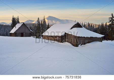 Wooden hut in the mountains. Winter landscape