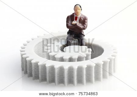 Businessman Figurine Sitting on the Gear