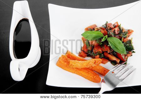 vegetable salad : cherry tomatoes and basil with sweet baked potato served on white plate with sauce boat full black soy sauce on wood high resolution hidef