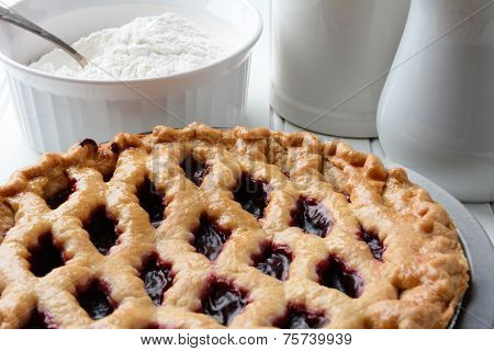 High angle shot of a fresh baked cherry pie with a lattice crust. A bowl of flour and pitchers fill the background. Horizontal format.