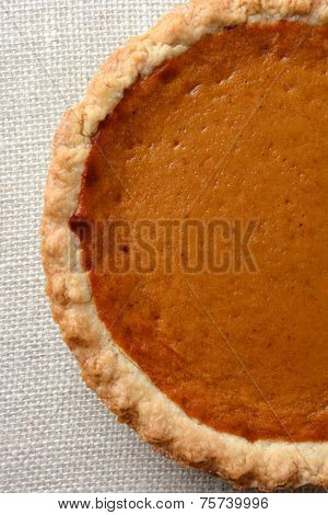 High angle shot of a Thanksgiving Pumpkin Pie.  Pumpkin pie is a traditional desert served on the American Holiday. Vertical format, only half the fie filling the frame.