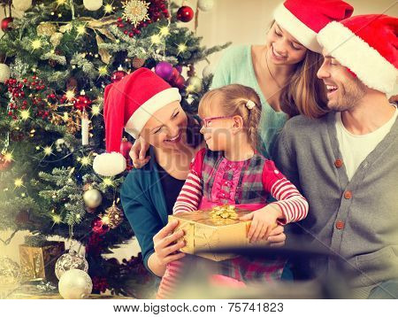 Christmas Family with Kids opening Christmas gifts. Happy Smiling Parents and Children at Home Celebrating New Year. Christmas Tree. Christmas scene