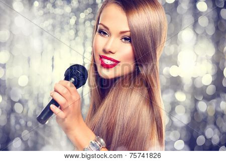 Singing Woman. Beautiful model Girl Singing. Beauty gorgeous lady with Microphone over holiday glowing Background. Singer. Karaoke song, party