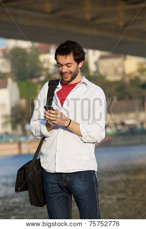 Young Man Sending Text Message On Mobile Phone