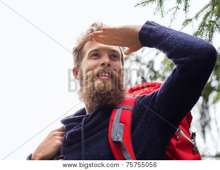 adventure, travel, tourism, hike and people concept - smiling man with beard and red backpack hiking