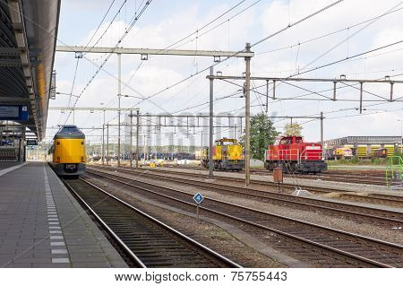 Platform Of Train Station With Yellow And Red Train Locomotives