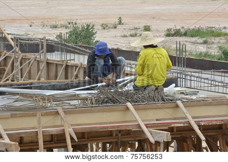 Two construction workers installing electrical conduit