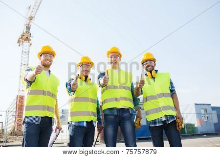 business, building, teamwork, technology and people concept - group of smiling builders in hardhats with tablet pc computer and clipboard showing thumbs up gesture outdoors