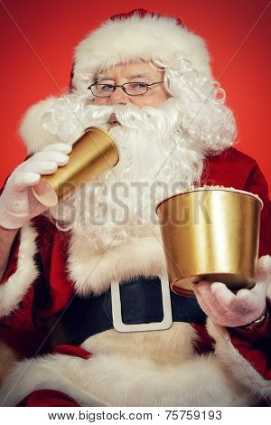 Close-up portrait of Santa Claus eating popcorn and drinking soda. Christmas. Red background.