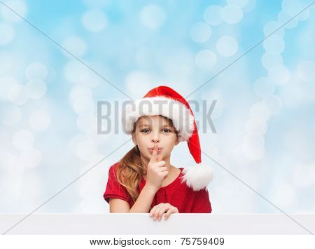 christmas, holidays, childhood and people concept - smiling little girl in santa helper hat with finger on her lips over blue lights background