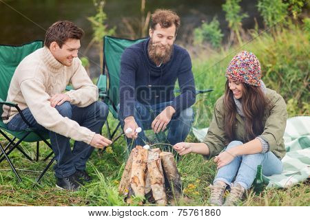adventure, travel, tourism and people concept - group of smiling friends with marshmallow sitting around bonfire in camping