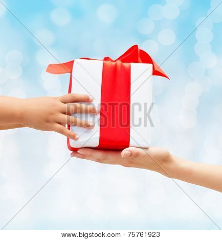 holidays, present, christmas, childhood and happiness concept - close up of child and mother hands with gift box over blue lights background