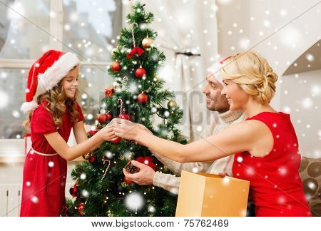family, christmas, holidays and people concept - smiling family in santa hats decorating christmas tree at home