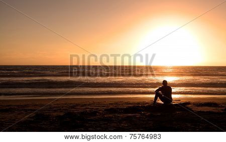 Surfer sitting on Surf board on the beach at sunset