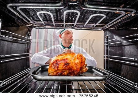 Chef prepares roast chicken in the oven, view from the inside of the oven. Cooking in the oven.