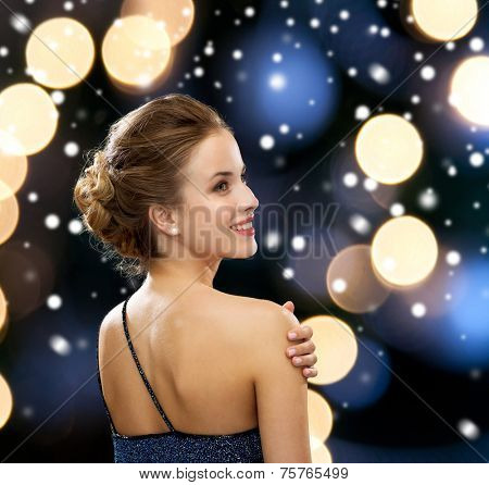 people, holidays, christmas and glamour concept - smiling woman in evening dress over black background over night lights and snow background from back