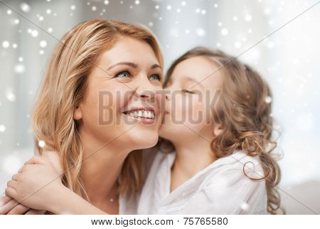 people, motherhood, family, winter and adoption concept - happy mother and daughter hugging and kissing at home