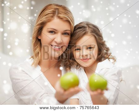 family, winter, healthy food and people concept - happy mother and daughter holding green apples at home
