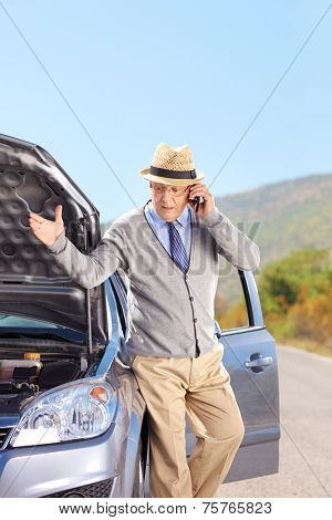 Vertical shot of a senior having a problem with his car on an open road