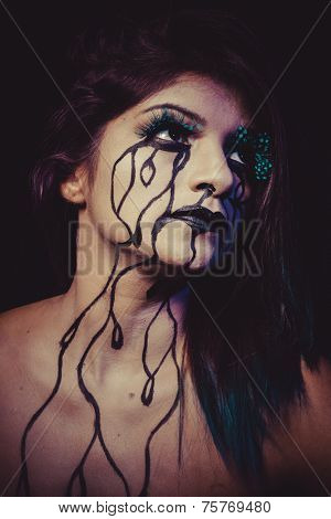 sorrow concept, crying woman with tears and makeup dark light