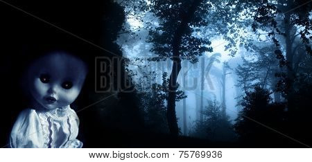 Vintage evil spooky doll and mysterious landscape of foggy forest