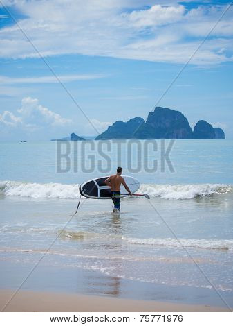 Young man stand up paddle boarding