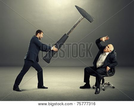 angry young businessman holding big hammer and screaming at frightened senior boss. photo at outdoor
