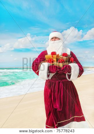 Santa Claus With Many Golden Gifts On Sea Beach