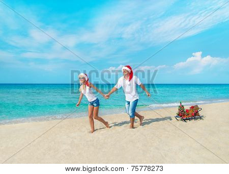 Happy Couple At Beach In Red Santa Hats With Gifts, Sled And Decorated Christmas Tree