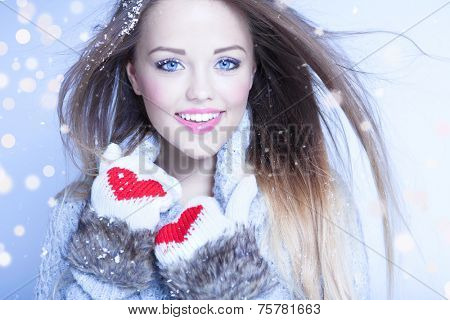 Beautiful happy young woman wearing winter gloves covered with snow flakes. Christmas snowing portrait concept.