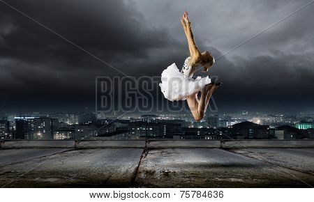 Young girl dancer jumping high in sky