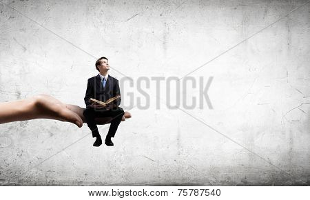 Young businessman sitting in palm with book