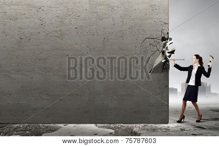 Young woman in business suit hitting hobnail with hammer