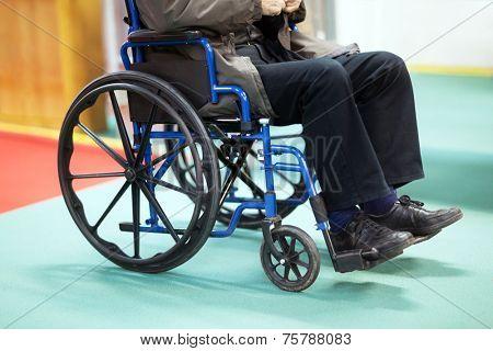 Disabled senior man using a wheelchair in a hospital ward