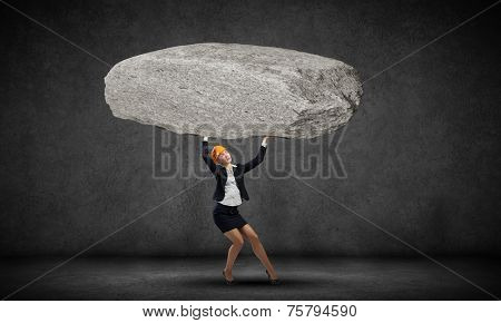 Young woman engineer lifting huge stone above head