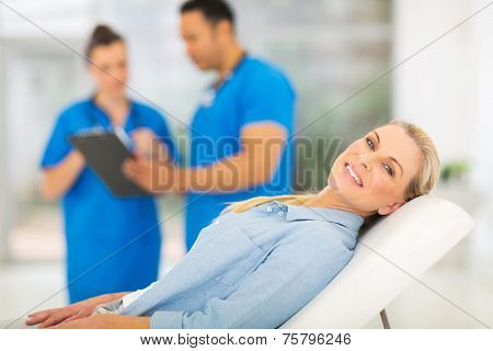 happy senior woman lying on doctor's examining bed and waiting for medical checkup