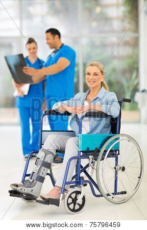 injured woman on wheelchair with doctors at medical office