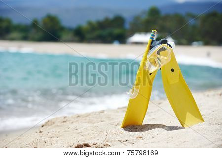 Mask with tube for snorkeling and flippers on the beach