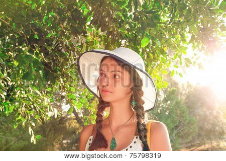 Summer closeup portrait of pretty tender beautiful young female face with clear skin and delicate complexion in the autumn evening sunshine in nature with big white hat and cute dreadlocks