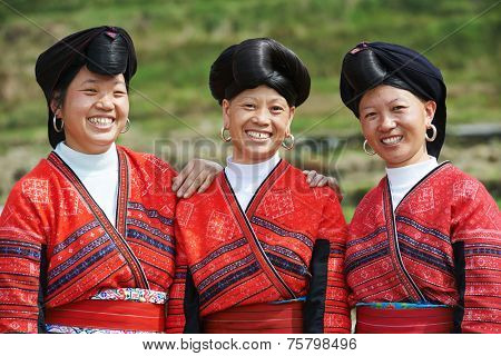 Group of happy chinese minority woman Yao in traditional dresses outdoors