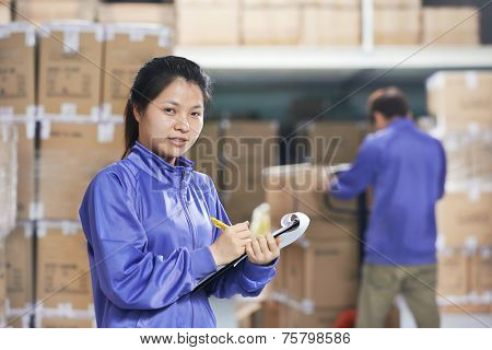 two young chinese workers in uniform in discussing warehousing system